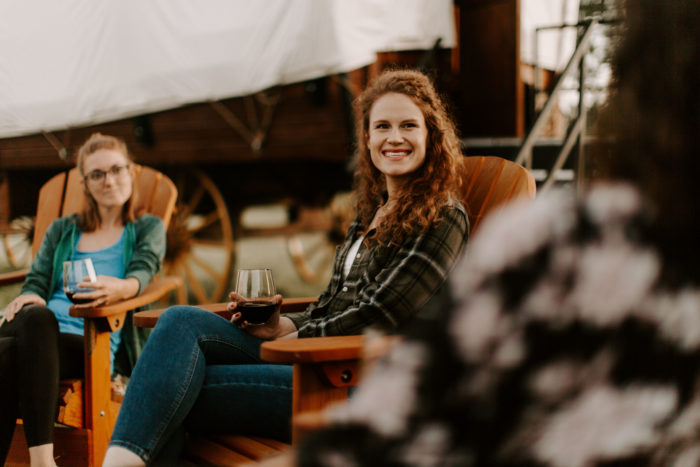 Women enjoying a glamping setting by sitting in chairs and talking