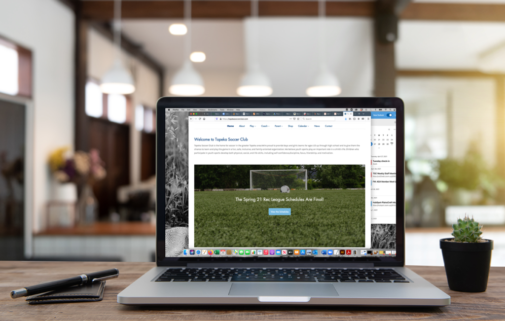 Laptop on a desk showing the Topeka Soccer Club website