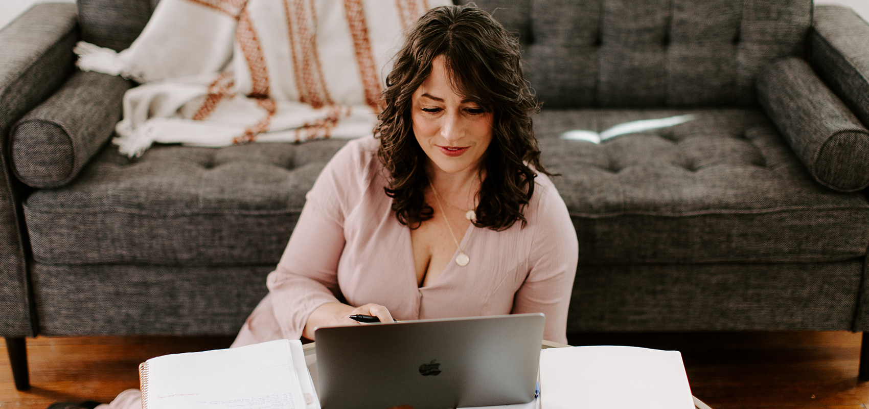 Melody, a brunette woman in a dusty pink dress, sits at her computer working
